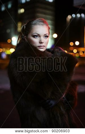 girl with dark hair in a fur coat