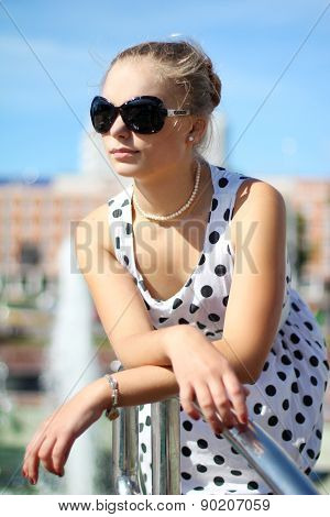 girl in a polka-dot dress and retro glasses