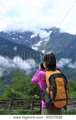 woman photographer taking photo at mountain peak in tibetchina