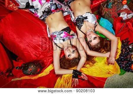 Two Oriental Beauty Lying On Pillows