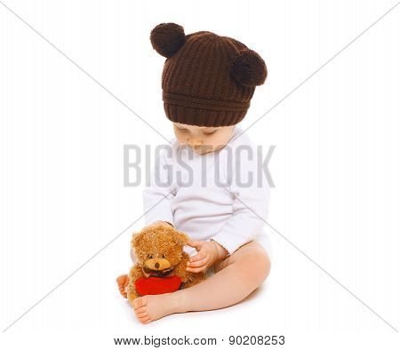 Baby In Knitted Brown Hat With Teddy Bear Toy