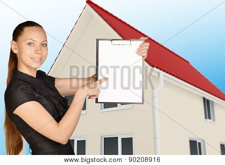 The girl on background of house holding clip board pointing forefinger