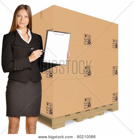 Woman standing on background of a cardboard boxes pallet and showing in clipboard