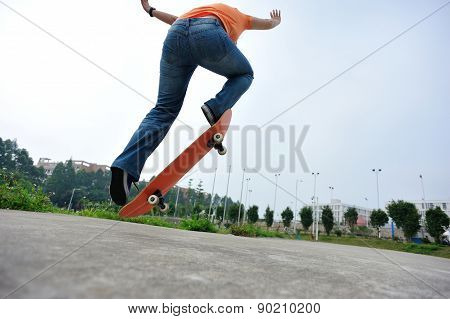 back of skateboarder doing  trick ollie outdoor