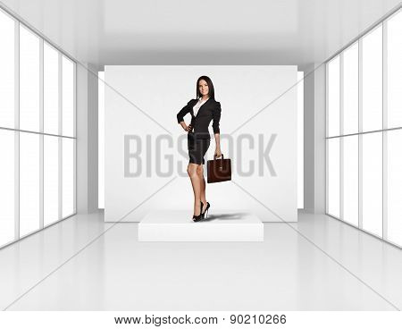 Young girl stands on the podium in an empty room light