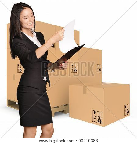 Young woman standing with cardboard boxes on pallet and looking in clipboard