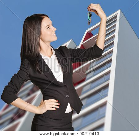 Woman standing on background of building and is holding keys from apartment