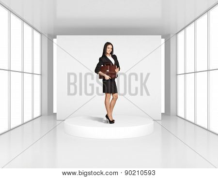 Woman with leather briefcase standing on the podium in bright room