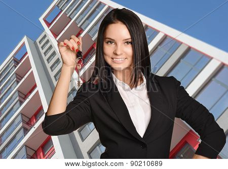 Beautiful girl standing on background of building and is holding keys