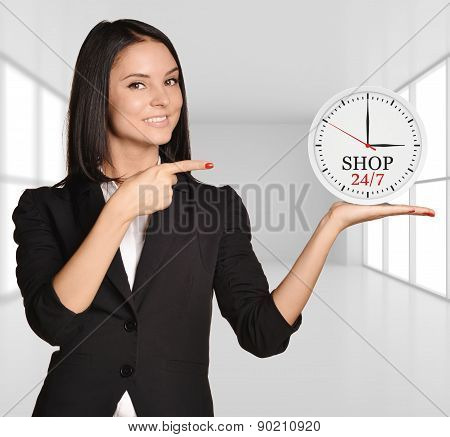 Office girl standing on background of light interior and holding clock with the inscription Shop