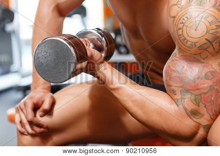 Power lifter working out with dumbbells in gym