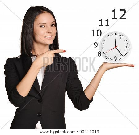 Office girl standing on white background and holding clock numbers flying off