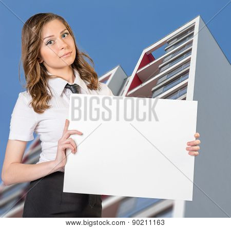 Girl standing on background of building and holding blank poster