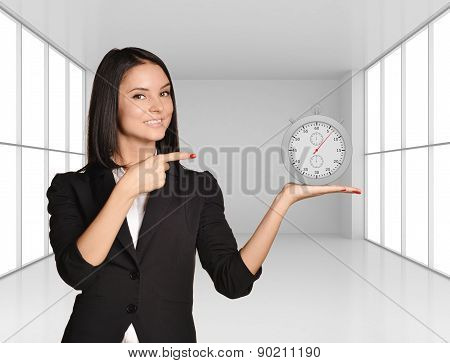 Office girl standing on background of light interior and holding stopwatch
