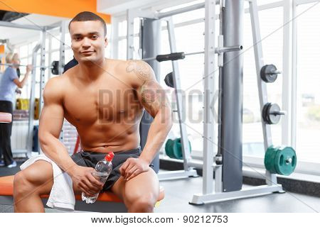 Man sitting with bottle and towel in gym