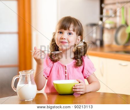 kid eating healthy food in kitchen