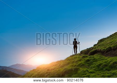 Silhouette Of Girl That Makes Trekking At Sunset