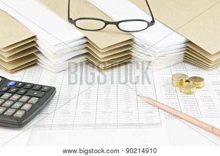 Brown Pencil And Pile Of Gold Coins With Spectacles