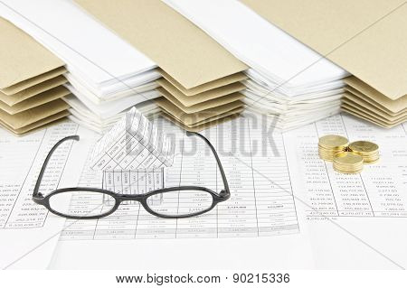 Spectacles And House With Pile Of Gold Coins