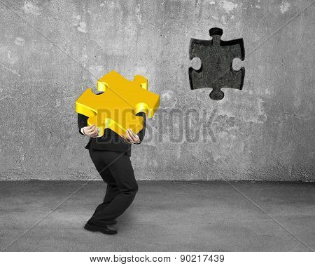 Businessman Carrying 3D Gold Jigsaw Puzzle Piece To Insert Hole