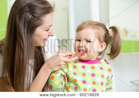 mother teaching child teeth brushing