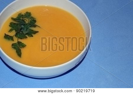 Pumpkin cream soup on blue background