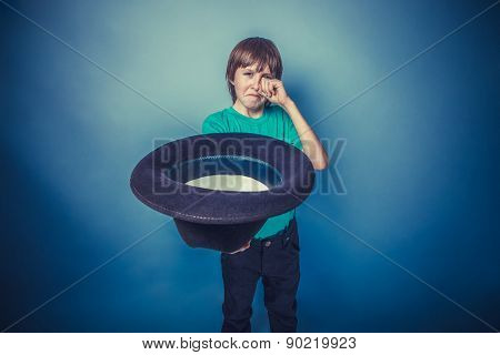 European-looking boy  of ten years beggar holding hat in hand on