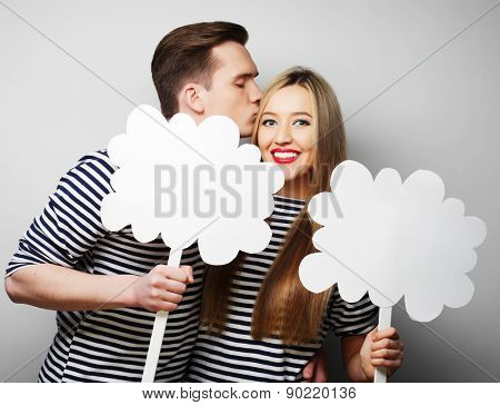 couple, love and family concept: amorous couple holding blank paper on stick.
