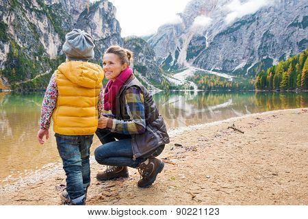 Mother Smiling And Kneeling Next To Daughter At Lake Bries