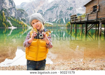Young Blonde Girl On Shores Of Lake Bries Holding A Camera