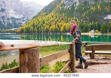Woman Hiker Rests On A Wooden Railing, Facing Lake Bries