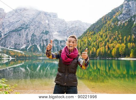 A Happy, Smiling Woman Hiker Giving Lake Bries Two Thumbs Up