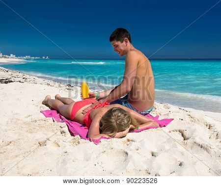 Man Applying Sun Lotion On A Woman Back