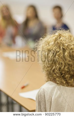 Caucasian Female Host In Front Of Group Of Women. Back View