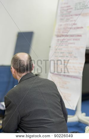 Male Lecturer Sitting In Front Of The Long Paper Presentation Sheet