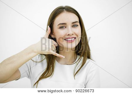 Young happy smiling brunette woman with call me gesture, against white background