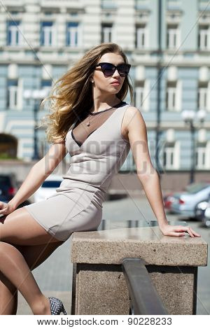 Portrait in full growth, Young beautiful blonde woman in beige short dress posing outdoors in sunny weather