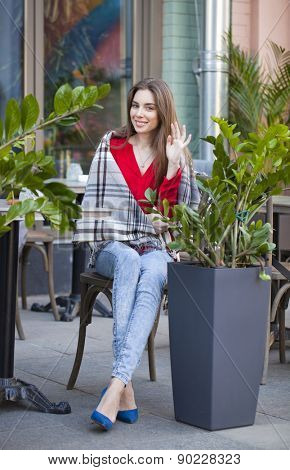 Young beautiful brunette girl sits in summer cafe in the street wrapped blanket