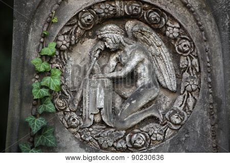 Mourning angel depicted in the abandoned tombstone at the Malostransky Cemetery in Prague, Czech Republic.