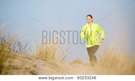 Woman Jogging Over Beach Dunes