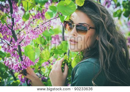 young urban woman with sunglasses outdoor shot among the spring flowers tree