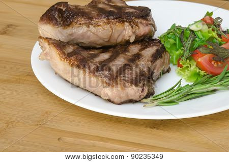 Grilled meat with salad at white plate on wooden background