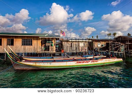 SABAH, MALAYSIA - SEPT 11: Sea gypsy boats moor besides the owners' wooden houses on Mabul Island, Sabah. Sea gypsies had lived in homes built on stilts planted into the seabeds for centuries.