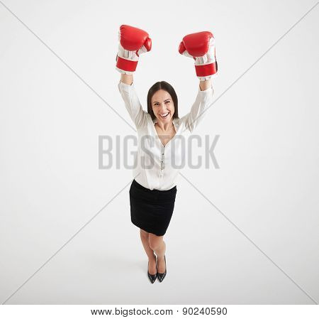 view from above young smiley woman in formal wear and red boxing gloves raising her hands up and looking at camera over light grey background