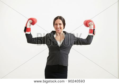 portrait of cheerful businesswoman in formal wear and red boxing gloves looking at camera over light grey background