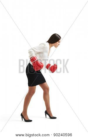 serious businesswoman in formal wear and red gloves standing in boxing pose and looking down over light background