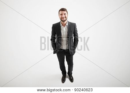 view from above of smiley businessman in formal wear looking up over light background