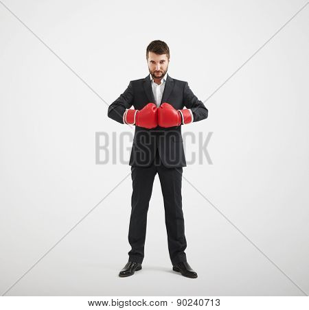 full length portrait of confided businessman in red boxing gloves looking at camera over light grey background