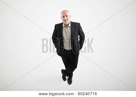 view from above of smiley senior businessman in formal wear looking up over light grey background