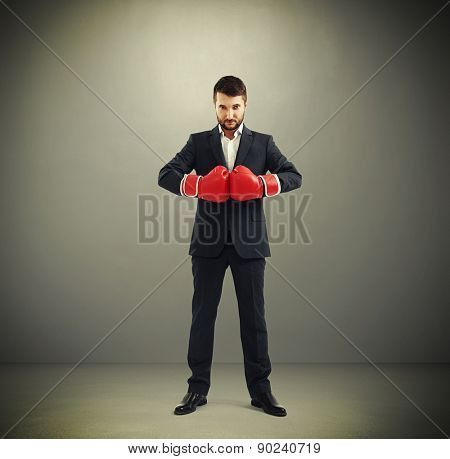 full length portrait of confided businessman in red boxing gloves looking at camera over dark background